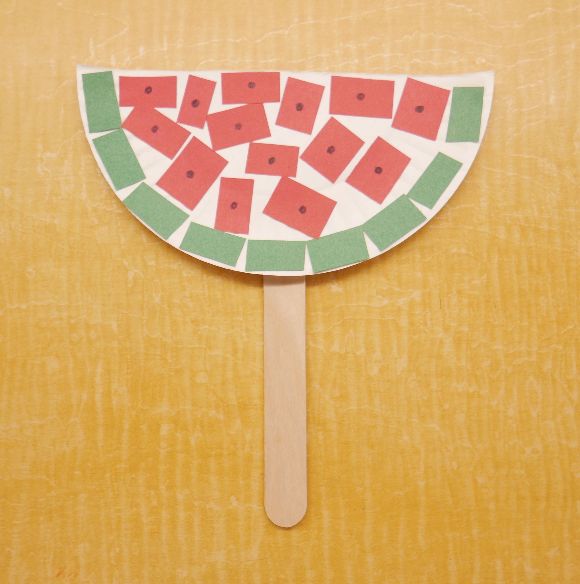 Watermelon Craft with half a paper plate and pieces of torn colored construction paper glued onto it