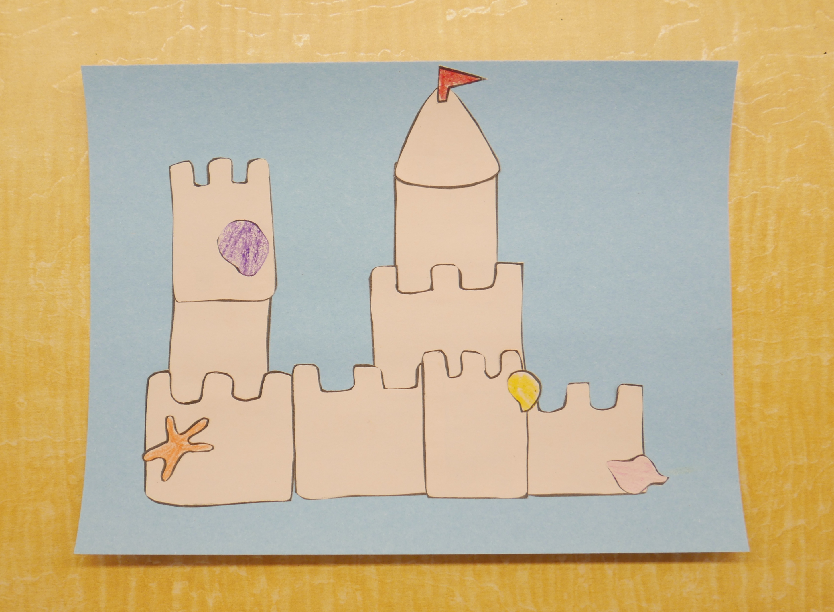 a papercraft that has various sandcastle pieces glued together on a blue background to make a sand c