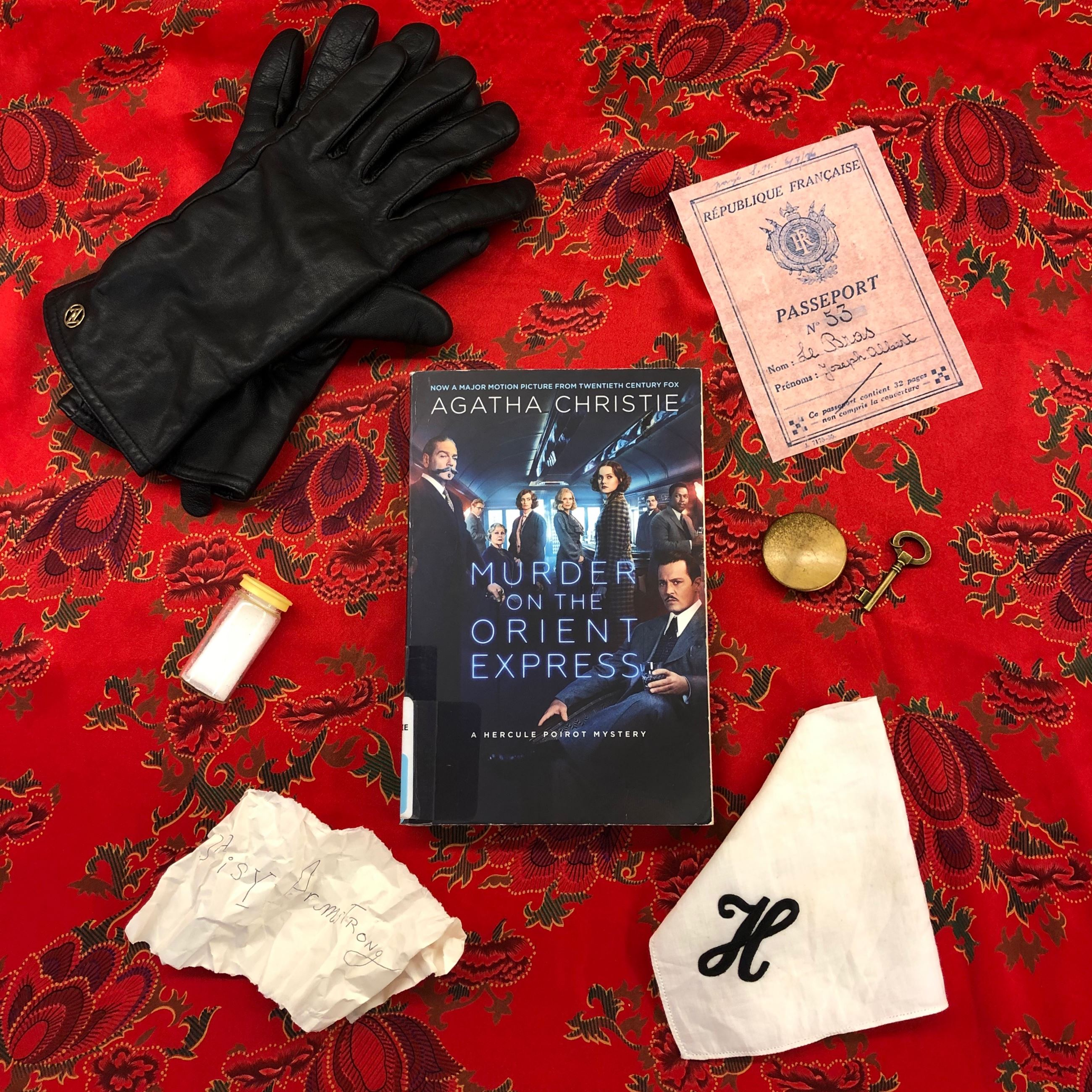 Book (Murder on the Orient Express by Agatha Christie) and gloves, passport, key, watch, in image