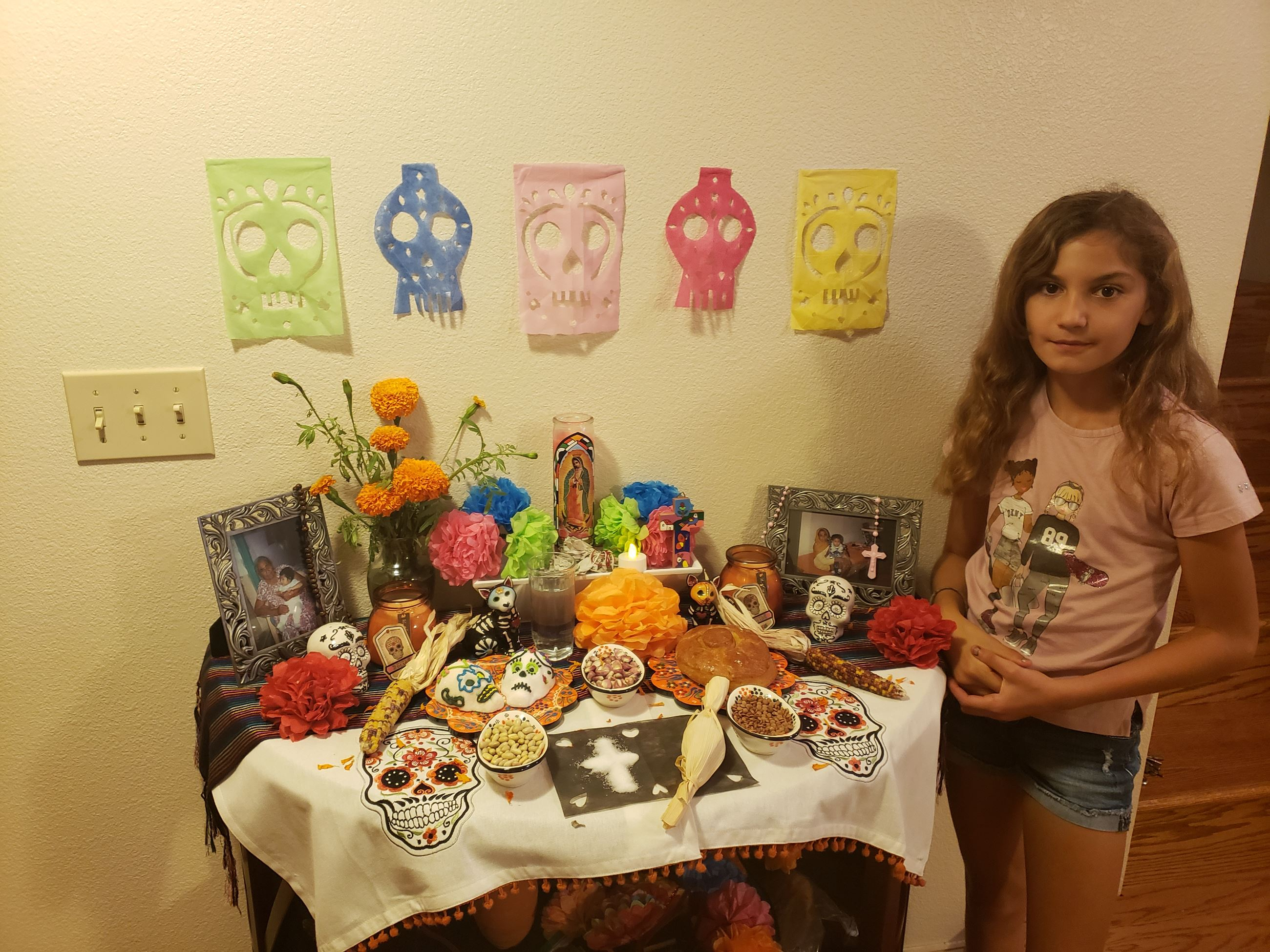 girl standing next to a day of the dead altar