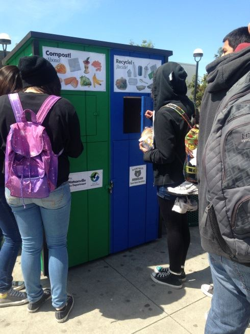 Students placing items in compost and recycle containers