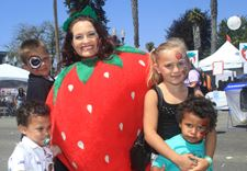 A woman in a strawberry costume with kids.