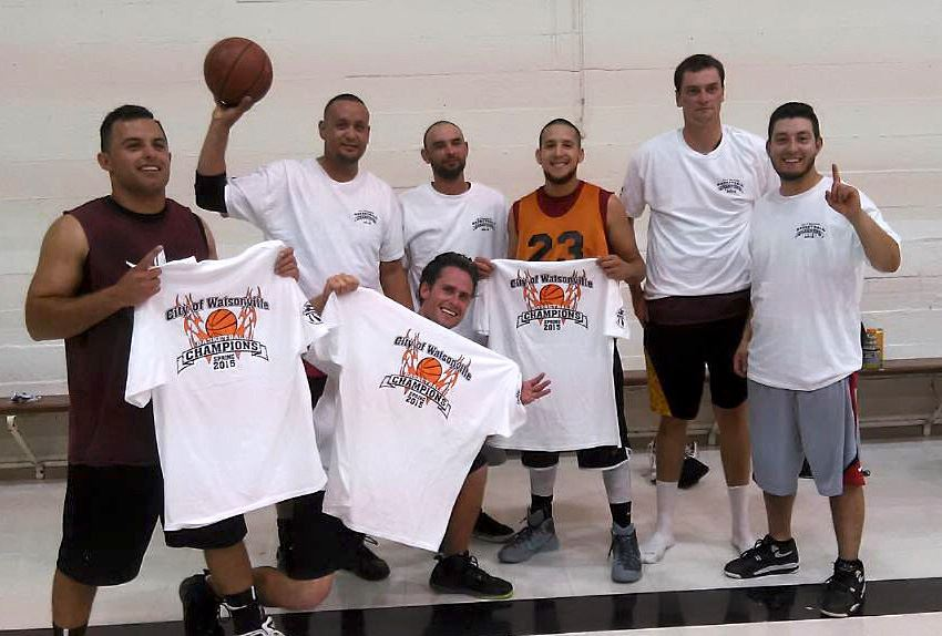 Mens basketball participants holding up champion shirts