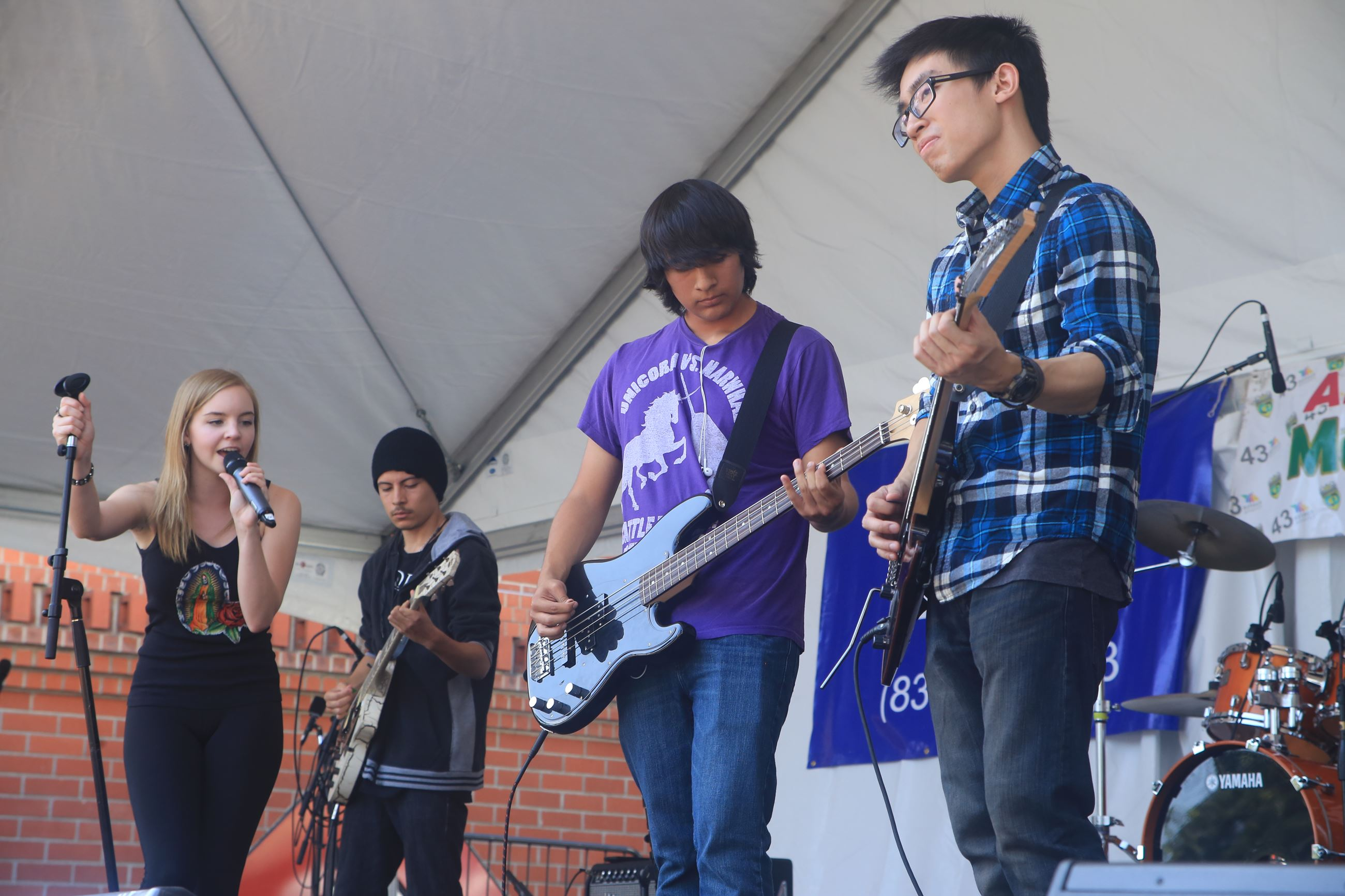 Teens playing and singing music on a stage