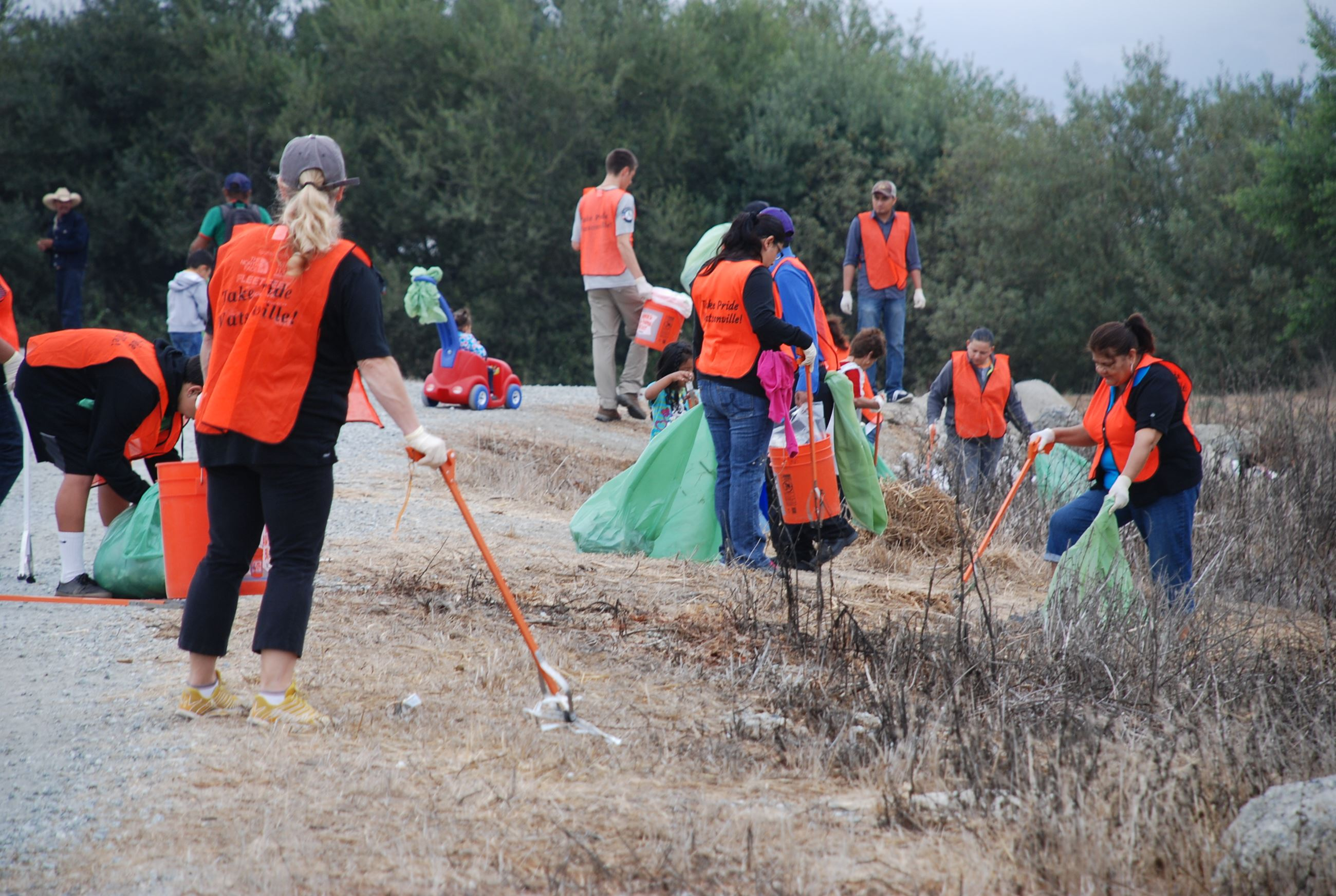 Volunteers picking up trash on the side of the road