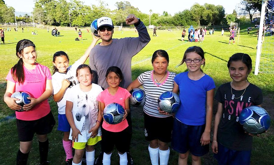 Volunteer coach with youth soccer participants