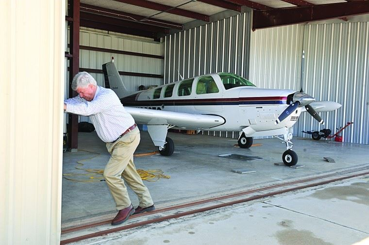 Man Opening Hangar Door with Airplane in Hangar