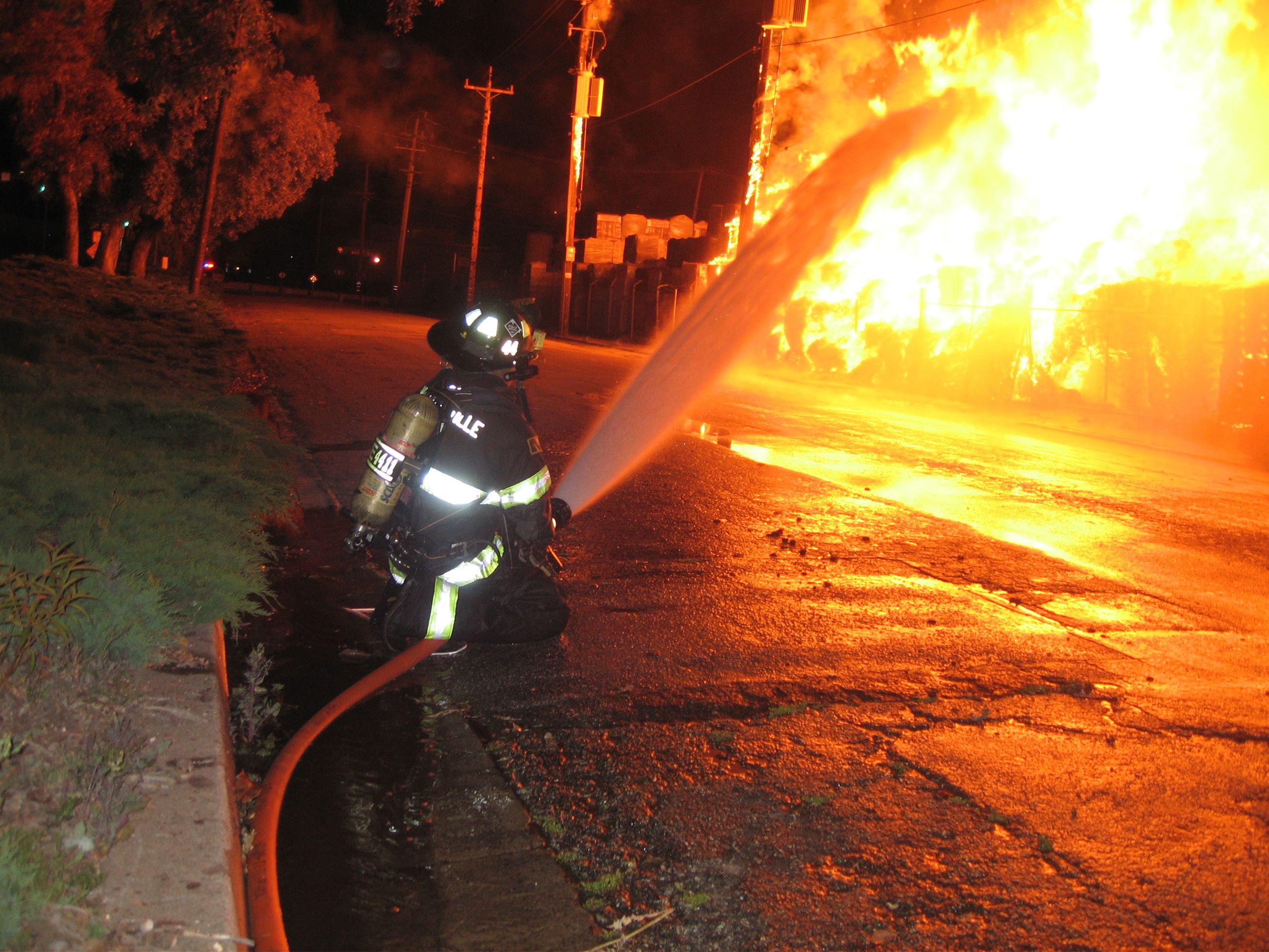 Firefighter with hose putting out a large fire at night
